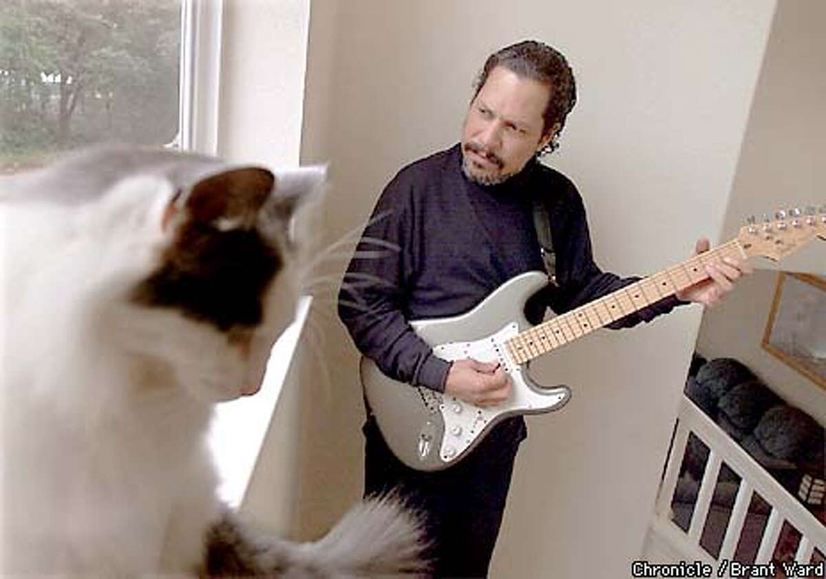 Shuggie Otis jammed in his Windsor home while his cat, affectionately called Tubby, enjoyed the music and the sun on it's back. By Brant Ward/Chronicle
