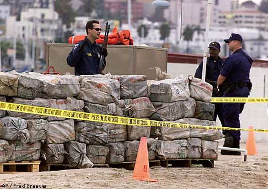 Coast Guard personnel guard part of an eight-ton load of cocaine at the Coast Guard Station Activities San Diego on Sunday, March 4, 2001. Authorities said a Belizean fishing vessel was carrying the drugs when it was intercepted by the Coast Guard near Acapulco, Mexico, on Feb. 24. The seizure, worth an estimated $500 million, is the fourth largest seizure in U.S. maritime history. (AP Photo/Fred Greaves) Photo: FRED GREAVES