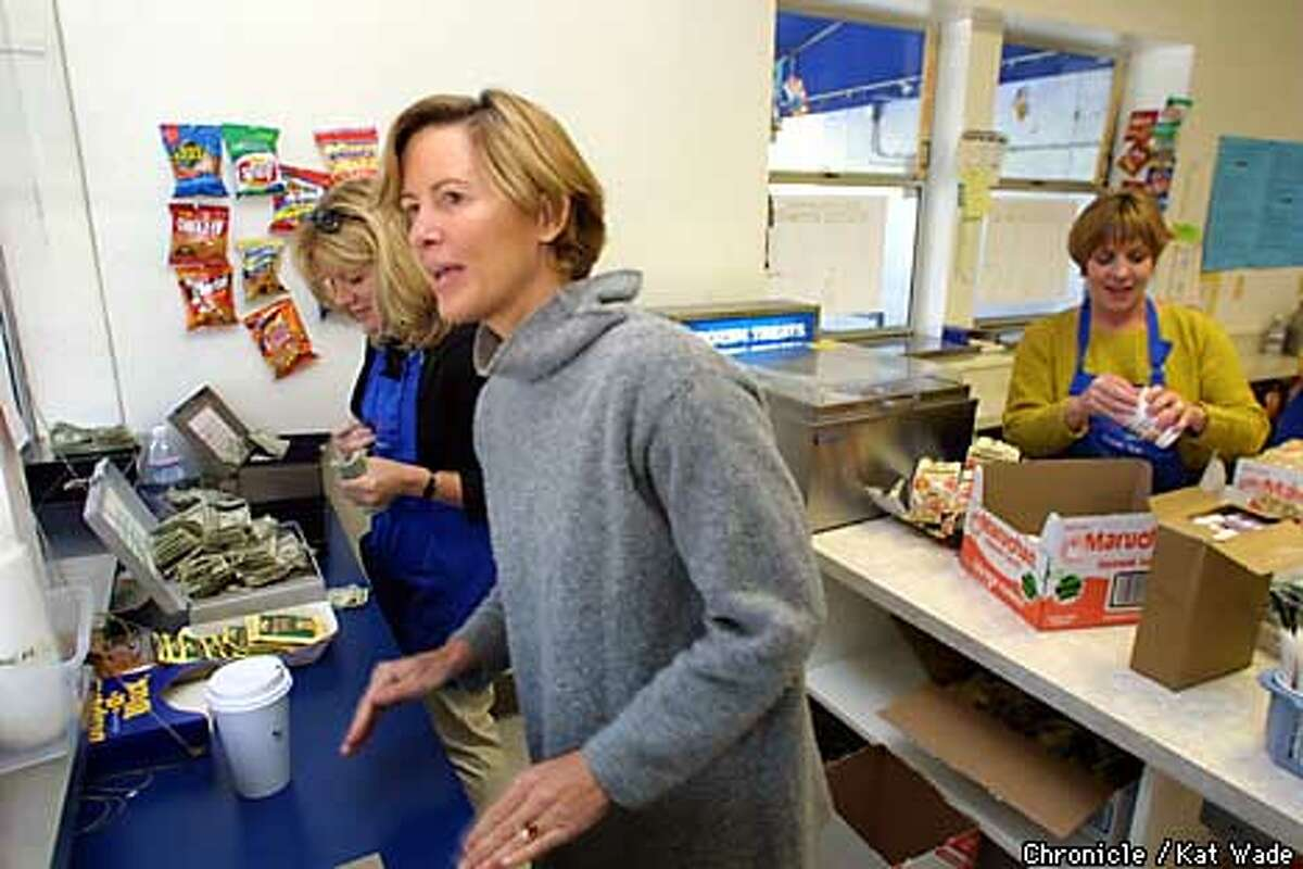 While, Betty Thompson, begins to count the cash, Sheila Nishioki serves the last few students at Orinda Intermediate School at the Bulldog Kennel, the schools parent run cafeteria. Working in the background is another parent, Pam Zitterman (CQ). SAN FRANCISCO CHRONICLE PHOTO BY KAT WADE