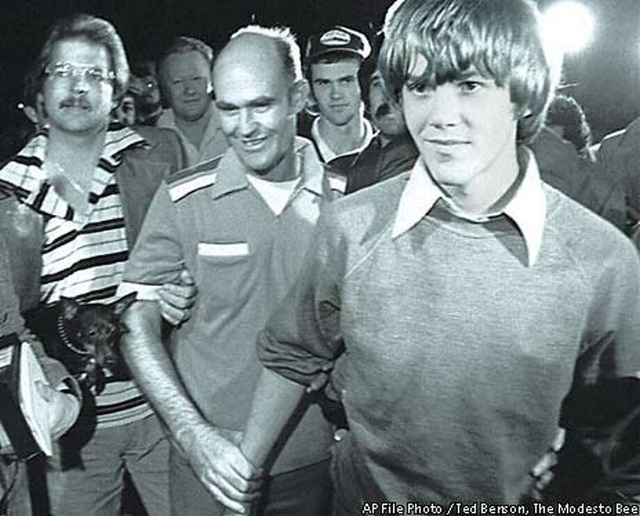 Steven Stayner, 14, is flanked by his father, Delbert (left) during a press conference after Steven and a young boy escaped from a sexual predator on Valentine's Day 1980 in Ukiah, Calif. In the background wearing a baseball cap is Steven's older brother, Cary, who would later become known as the Yosemite Serial Killer. Photo: AP File Photo/Ted Benson,  The Modesto Bee