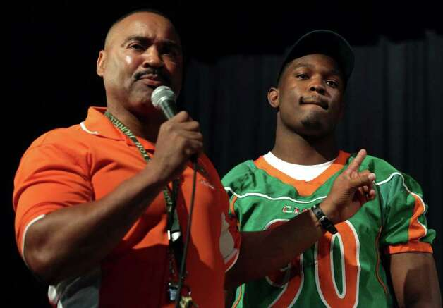 With tears welling up in his eyes, Sam Houston H.S. coach Gary Green, left, tells how Javonte Magee, who signed with Baylor University, was adopted by Mary Griffin, making sure the young player stayed on the right track while growing up. Seven football players from Sam Houston High School committed to college teams on National Signing Day.  Wednesday, Feb. 1, 2012. Bob Owen/Express-News Photo: BOB OWEN, San Antonio Express-News / © 2012 San Antonio Express-News