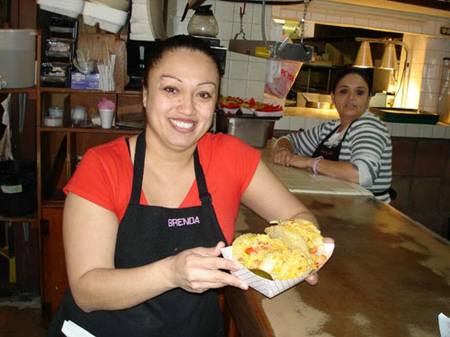 Ray's Drive-Inn waitress Brenda Serna shows off the restaurant's famous puffy tacos. Photo by Miranda Koerner