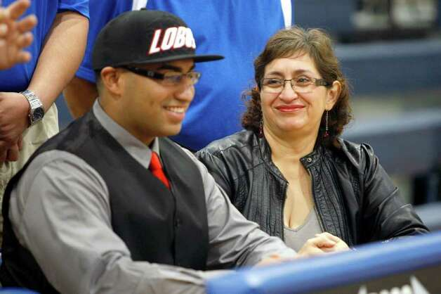 Elsa Vizcaino, right, smiles Wednesday Feb. 1, 2012 at Lanier High School moments after her son Lanier football player Johnny Vizcaino signed a letter of intent to play at the University of New Mexico, becoming one of the first two football players in Lanier's long history to sign national letters of intent to four-year institutions, according to school officials. The other was teammate Xavier Perez Coley who signed at the same time to play at Seton Hill University.