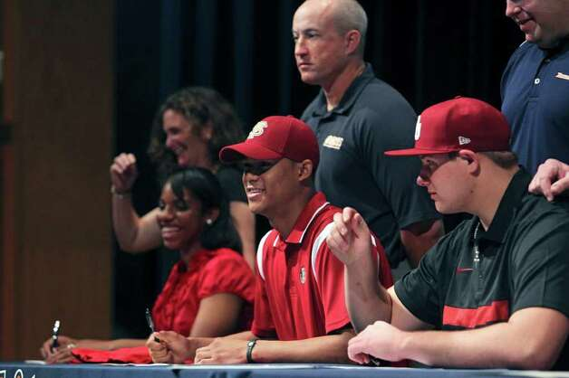 SPORTS   Athletes including Colin Blake (center) put on hats after signing during college signing day for athletes at Brandeis High School on February 1, 2012 Tom Reel/ San Antonio Express-News Photo: TOM REEL, SAN ANTONIO EXPRESS-NEWS / © 2012 San Antonio Express-News  MAGS OUT; TV OUT; NO SALES; SAN ANTONIO OUT; AP MEMBERS ONLY; MANDATORY CREDIT; EFE OUT