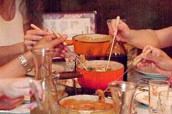 A variety of fondues are presented for dinner at Fondue Fred's in Berkeley. Photo by Gina Gayle/The SF Chronicle.
