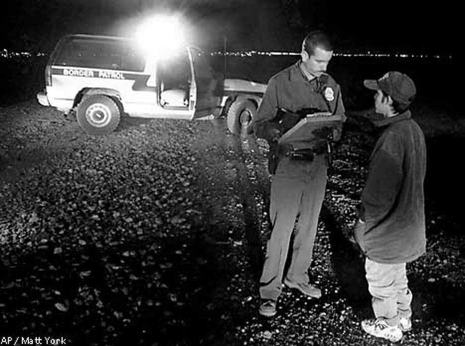 FILE-- U.S. Border Patrol agent Brent Barber takes information from a Mexican citizen, early morning hours of April 10, 2000, in Douglas, Ariz. Hundreds of Mexicans try to illegally cross into the United States via Aqua Prieta, Mexico every day. At least 66 illegal immigrants have died this year making their way through Arizona, the most the Border Patrol has ever recorded in the state. Last year, 40 people died crossing Arizona's border. (AP Photo/Matt York) Photo: MATT YORK