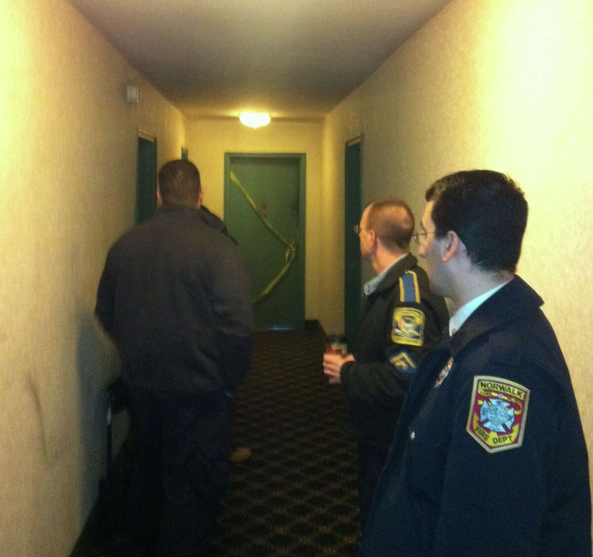 State and Norwalk fire investigators inspect a hallway of an apartment building in Norwalk, Conn. where two residents were hospitalized following a fire on Tuesday, Jan. 31, 2012. The residents were identified by neighbors as Judy O'Brien 62 and her mother, Marjorie Johnson, 92, mother. O'Brien died the following day.