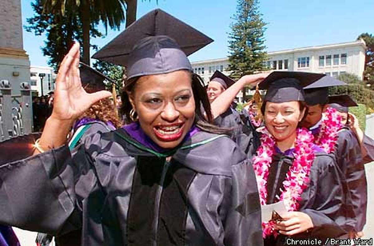 Cupcake Brown grabbed her graduation cap as the wind picked up around University of San Francisco Sunday. She is graduating near the top of her class at the law school here after a difficult life which included prostitution and drug abuse. In background is her dear friend Lourdes Ejia. By Brant Ward/Chronicle