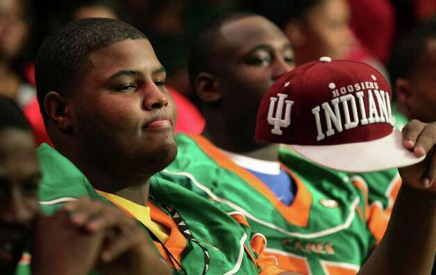 Sam Houston H.S. standout Ralpheal Green, who signed with Indiana University, hold up his college cap during the signing ceremony at the highschool.  Seven football players from Sam Houston High School committed to college teams on National Signing Day.  Wednesday, Feb. 1, 2012. Bob Owen/Express-News Photo: BOB OWEN, San Antonio Express-News / © 2012 San Antonio Express-News
