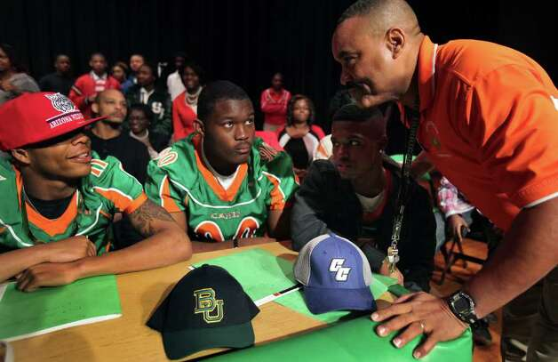Sam Houston H.S. Football Coach Gary Green, right, has a word with Leo Thomas, left to right, Javonte Magee, and JeQuan McBride before the signing ceremony at the high school.  Seven football players from Sam Houston High School committed to college teams on National Signing Day.  Wednesday, Feb. 1, 2012. Bob Owen/Express-News Photo: BOB OWEN, San Antonio Express-News / © 2012 San Antonio Express-News