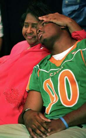 Mary Griffin, cradles her adopted son, Sam Houston's standout player Javonte Magee, after he signed with Baylor University, at the high school.  Seven football players from Sam Houston High School committed to college teams on National Signing Day. , Wednesday, Feb. 1, 2012. Bob Owen/Express-News Photo: BOB OWEN, San Antonio Express-News / © 2012 San Antonio Express-News