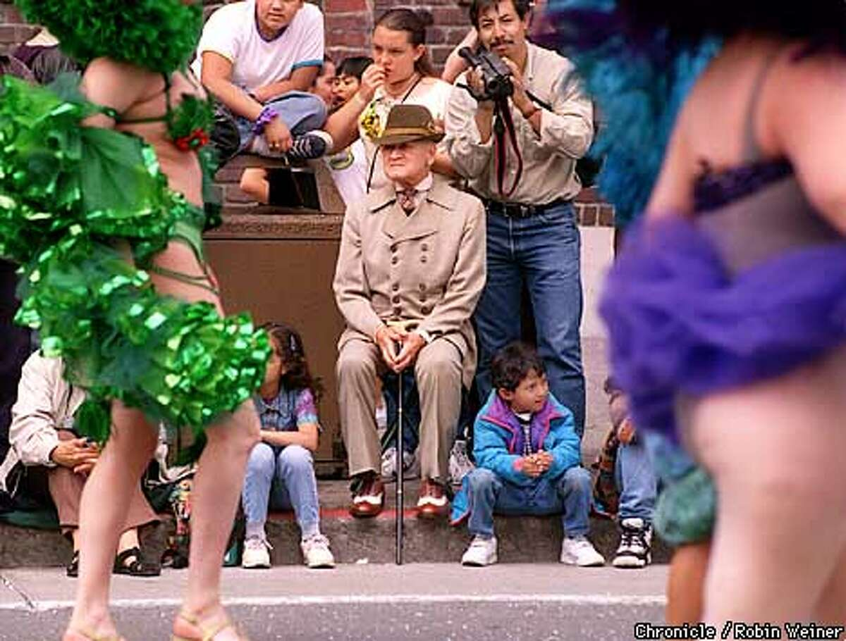 Major Frank Cook of San Francisco sits along packed sidewalks to watch the Carnaval parade go by through the Mission district. Robin Weiner/The Chronicle