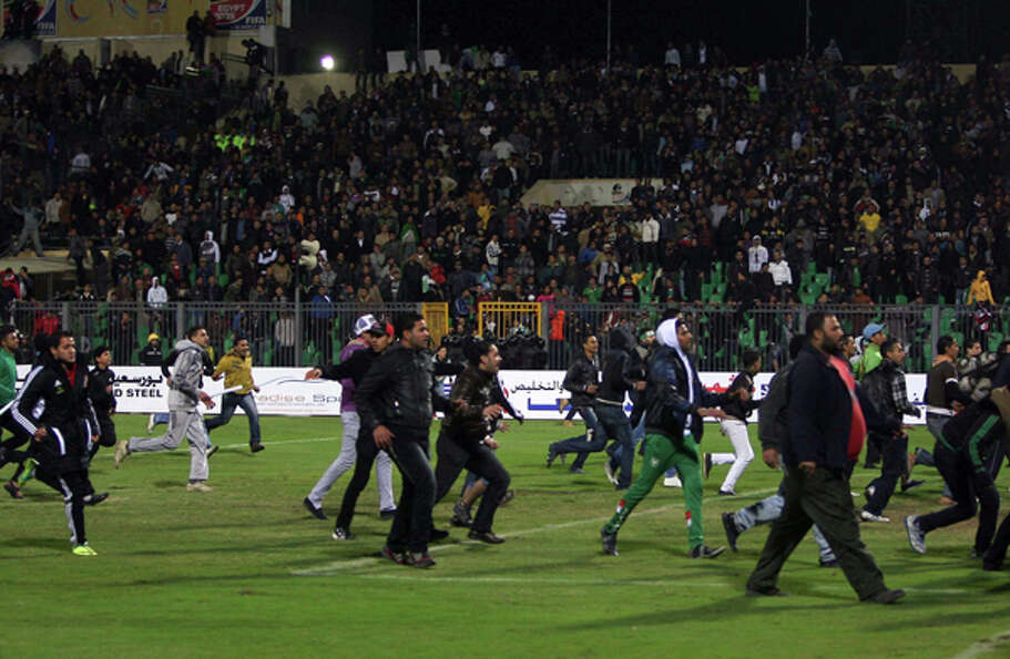 Egyptians football fans rush to the fiels during clashes that erupted after a football match between