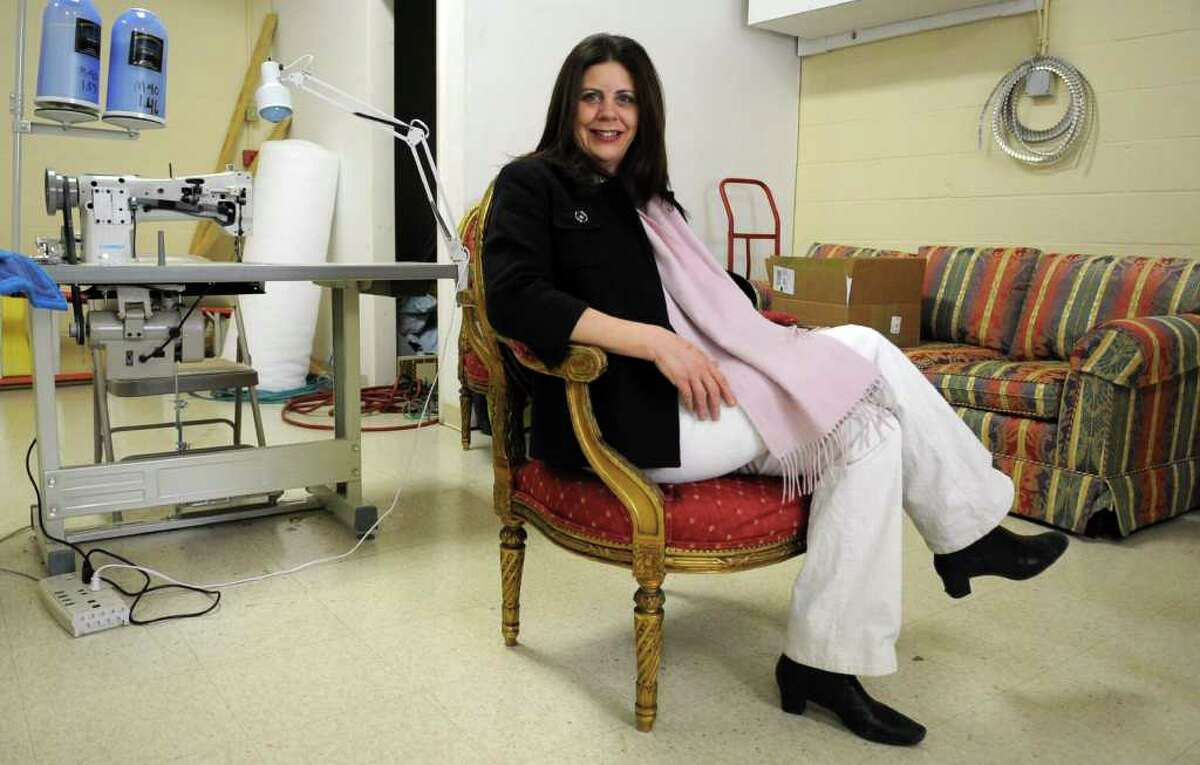 Christina Spano Manowitz poses for a photo with a chair she will be re-upholstering at her custom interior decorating business, Christina's on Magee, on Wednesday, February 1, 2012.