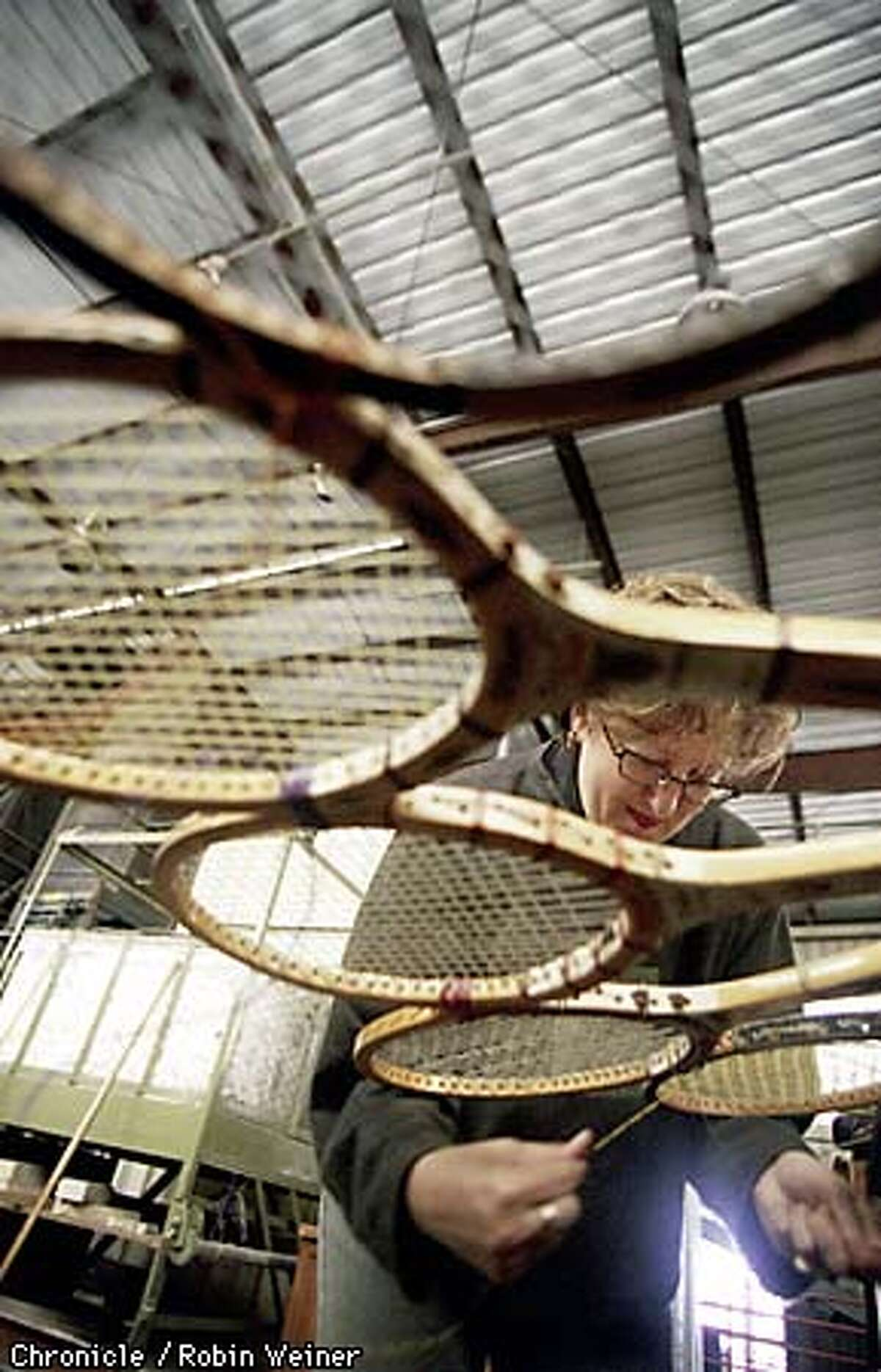 Susan Cronenwett turns wooden tennis racquets into a flower sculpture at her work space a the San Francisco garbage dump, where she is the latest artist-in-residence. BY ROBIN WEINER/THE CHRONICLE