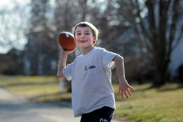 Seven-year-old Zach Anderson plays a game of football outside his home in Stratford Wednesday, Feb. 1, 2012, an unseasonably mild day. Photo: Autumn Driscoll / Connecticut Post