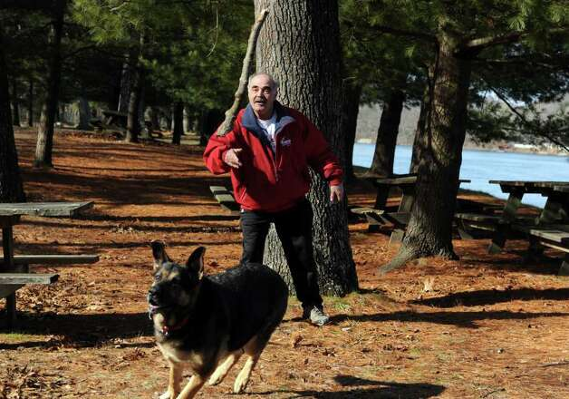 Vincent Pelaccia, of Shelton, throws a stick to his dog, Kayla, Wednesday, Feb. 1, 2012, an unseasonably mild day, at Indian Well State Park in Shelton, Conn. Photo: Autumn Driscoll / Connecticut Post