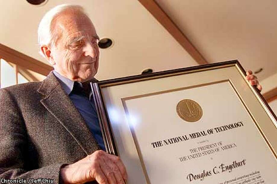 Douglas Engelbart displays his award of the National Medal of Technology at his Atherton home on Wednesday afternoon. Among his claims to fame is his invention of the computer mouse while at Stanford Research Institute in Menlo Park. Photo by Jeff Chiu / the Chronicle. Photo: JEFF CHIU
