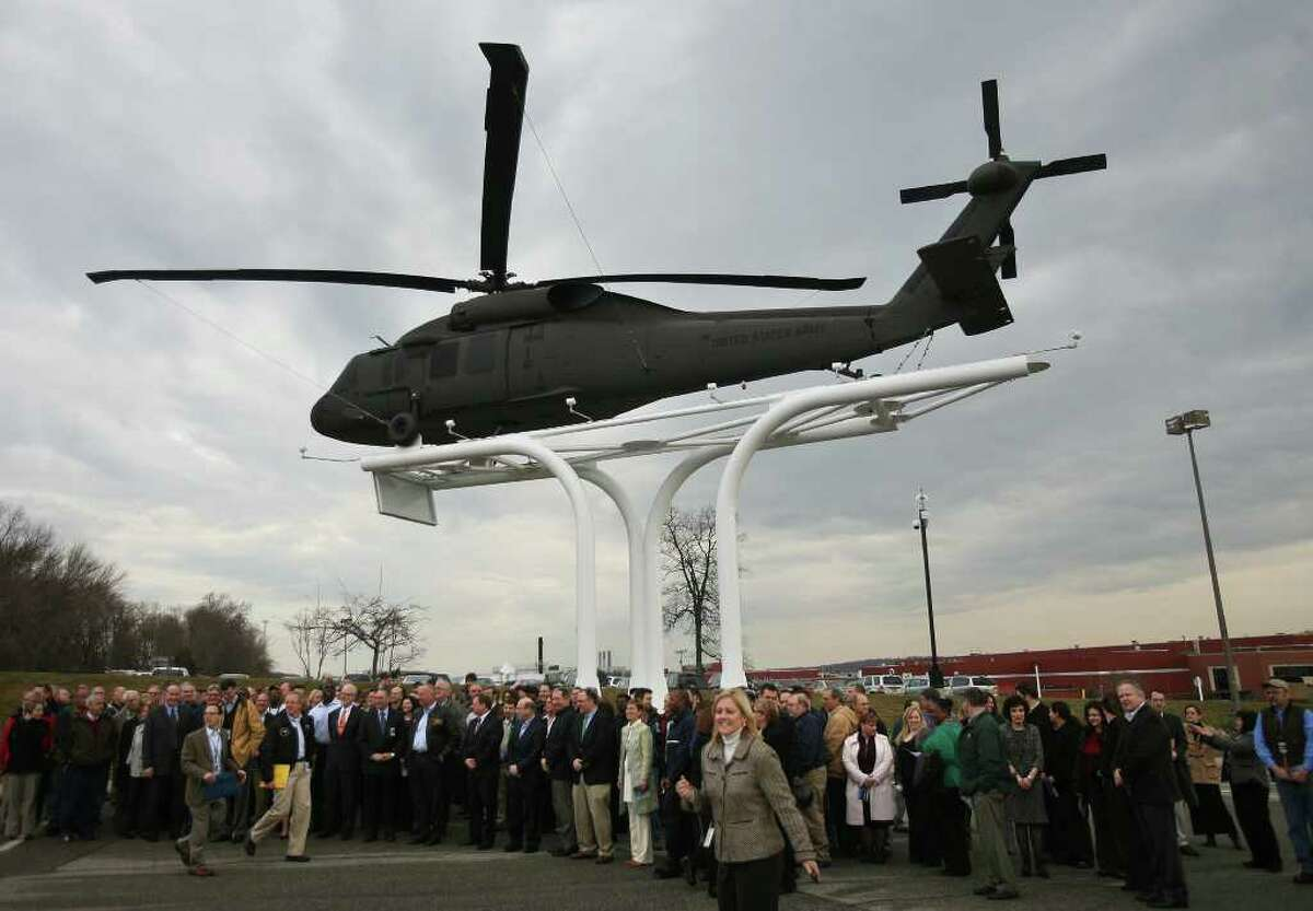Sikorsky employees gather for a group photo beneath the UH-60 Black Hawk helicopter unveiled in front of the company headquarters and factory on Main Street in Stratford on Wednesday, February 1, 2012.