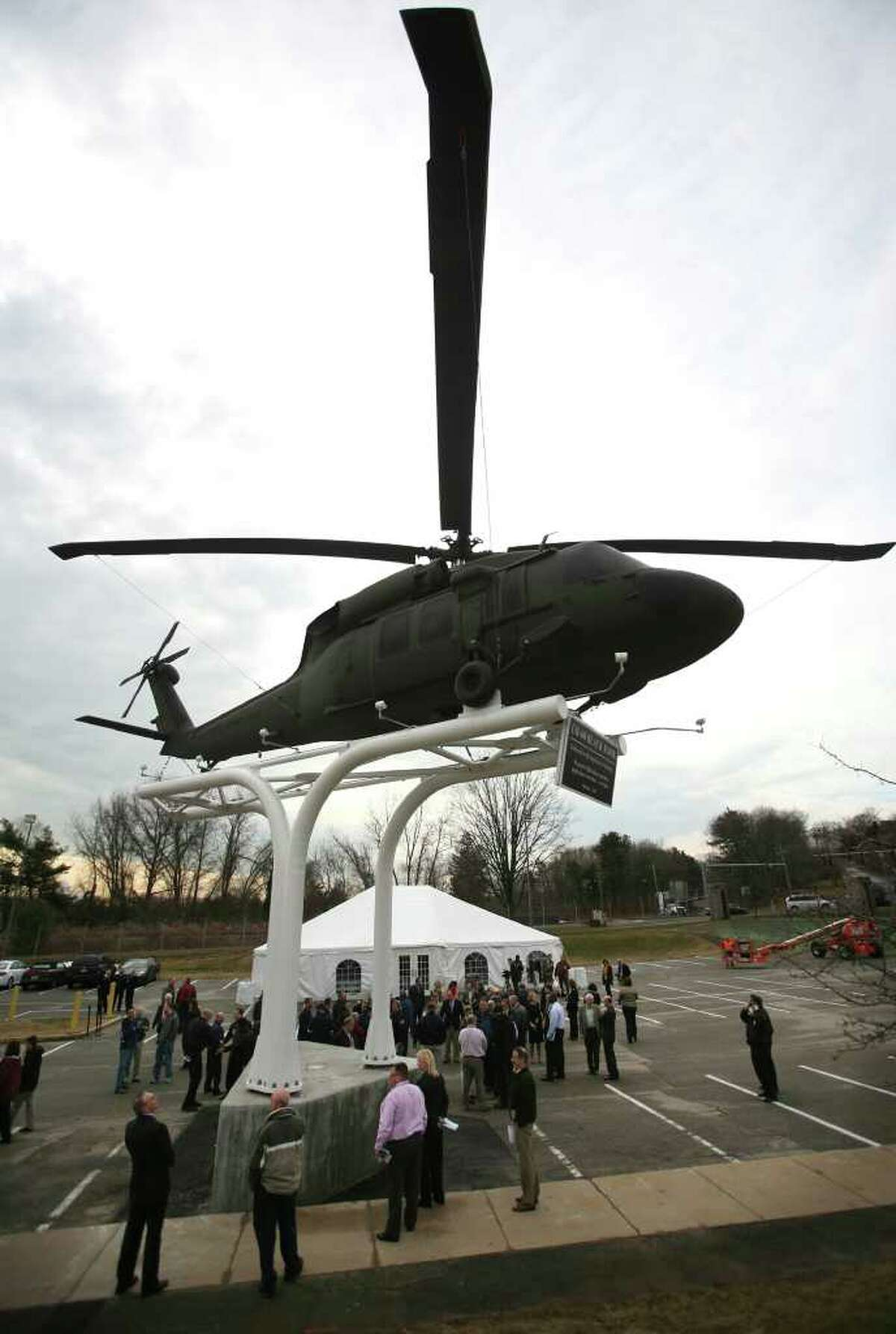 Sikorsky employees gather around the UH-60 Black Hawk helicopter unveiled in front of the company headquarters and factory on Main Street in Stratford on Wednesday, February 1, 2012.