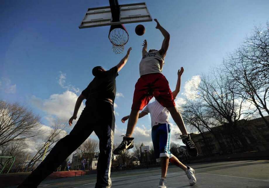From left, 21-year-old UAlbany students Brian Vigue, Matt Cillis and Brian Tahlor enjoy a mild winter day playing basketball in a park on Wednesday, Feb. 1, 2012 in Albany, N.Y.  (Lori Van Buren / Times Union) Photo: Lori Van Buren
