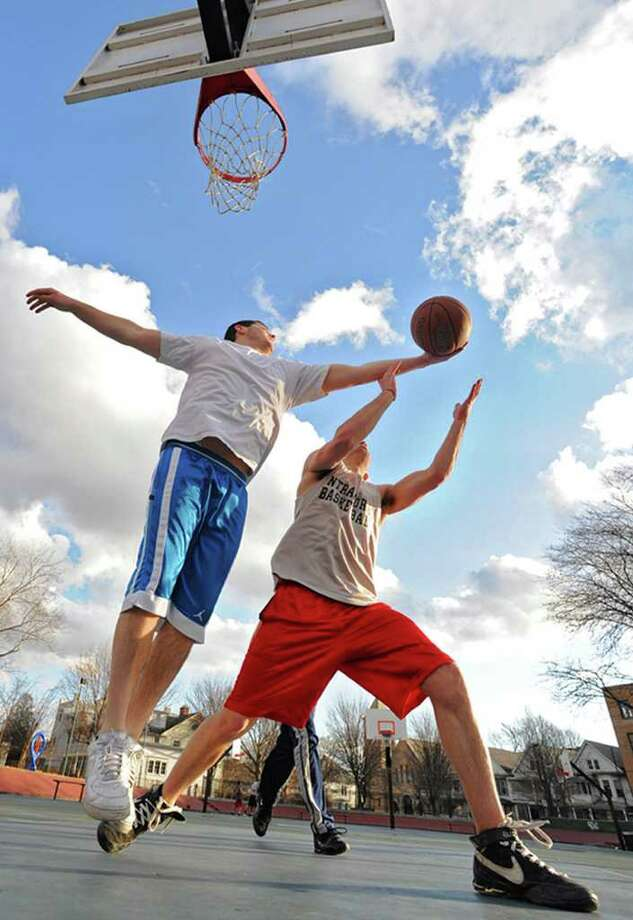 From left, 21-year-old UAlbany students Brian Tahlor, Matt Cillis and Brian Vigue (in back) enjoy a mild winter day playing basketball in a park on Wednesday, Feb. 1, 2012 in Albany, N.Y.  (Lori Van Buren / Times Union) Photo: Lori Van Buren
