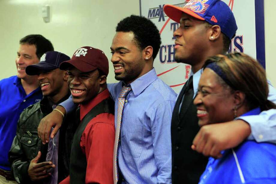 Next to their coach, Willie Amendola, left, and principal, Delic Loyde, right, Dekaney High School football players at left, Patrick Martin, Trey Williams, Myles Curl, and Armand Nance pose for a picture after signing their letter of intents on National Signing Day at Dekaney High School Wednesday, Feb. 1, 2012, in Spring. 