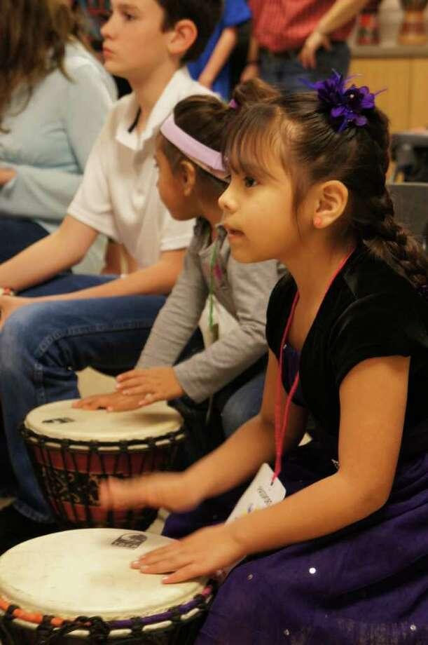 Pre-K student Letty Huerta plays along with Nina Rodriguez's Unlock the Rhythm workshop at the Sunshine Cottage School fine arts night.