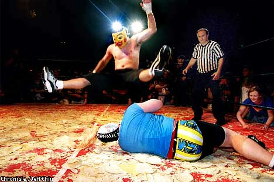 Super Pulga gives a legdrop to the fallen Doctor Loco during their match at Incredibly Strange Wrestling at the Fillmore on Friday night in San Francisco. Incredibly Strange Wrestling returns to the Fillmore on May 5. Photo by Jeff Chiu / The Chronicle. Photo: JEFF CHIU