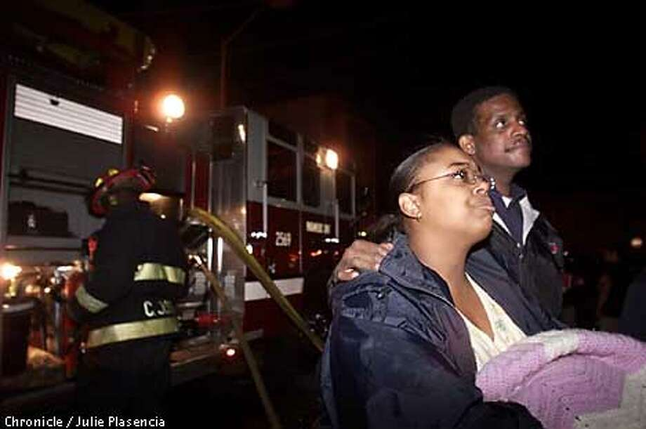 Anna Jackson is consoled by neighbor Kieth Robinson while fire fighters work on putting out the fire that has taken her home during a fire that spread over 14 blocks in West Oakland.  (JULIE PLASENCIA/THE CHRONICLE) Photo: JULIE PLASENCIA