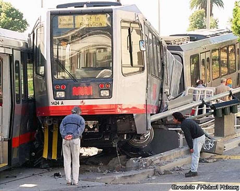 MUNI DERAIL/C/23JUN97/MN/MJM  Passersby stop to inspect the damage from a Muni derailment at 18th and Church Street early this morning.  Photo by Michael Maloney Photo: MICHAEL MALONEY