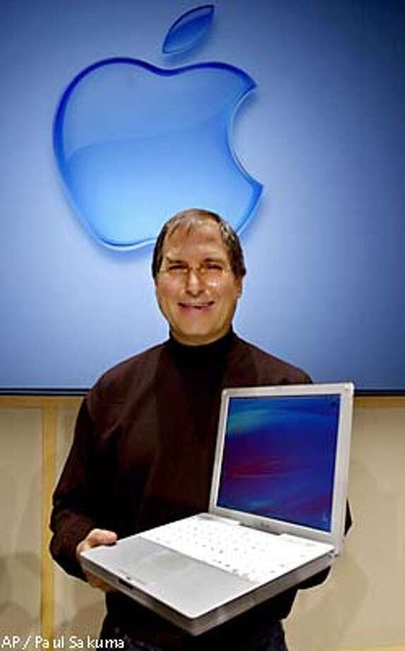 Apple Computers Inc. chief executive officer Steve Jobs holds up the new laptop iBook at a press conference at Apple headquarters in Cupertino, Calif., Tuesday, May 1, 2001. The new ibook will be available in mid-May with a retail price of $1,299 and has a battery life of 5 hours with built-in modem, firewire, ethernet, wireless communications, a 12.1-inch screen and weighs 4.9 pounds. (AP Photo/Paul Sakuma) Photo: PAUL SAKUMA