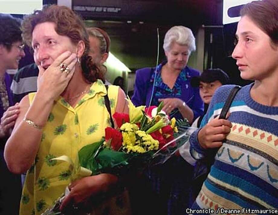 Kosovar refugee Nazmije Morina(cq), 40, (holding flowers) and her family are welcomed at San Francisco International Airport. They are being taken in by St. Nicholas Parish in Los Altos. Sister Marilyn Lacey with Catholic Charities places her hand on Nazmije's shoulder, while Sister Rosheen Glennon from St. Nicholas Parish (white hair, background) approaches Vlorent(cq), 11, and his sister (far right) Behare(cq), 19. CHRONICLE PHOTO BY DEANNE FITZMAURICE Photo: DEANNE FITZMARUICE