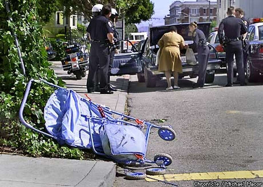 Crash involving Rabia Khouja pushing a stroller with her 10 month old son Yusuf Khouja and walking with 2 1/2 year old Mohammed when they were struck by a car in the crosswalks at the corner of Washington and Gough in SF. The driver of the vehicle that struck the trio gathers her belongings from the truck of her car in the background, being assisted by police. Driver stated that the brake failed and was unable to stop. by Michael Macor/The Chronicle Photo: MICHAEL MACOR