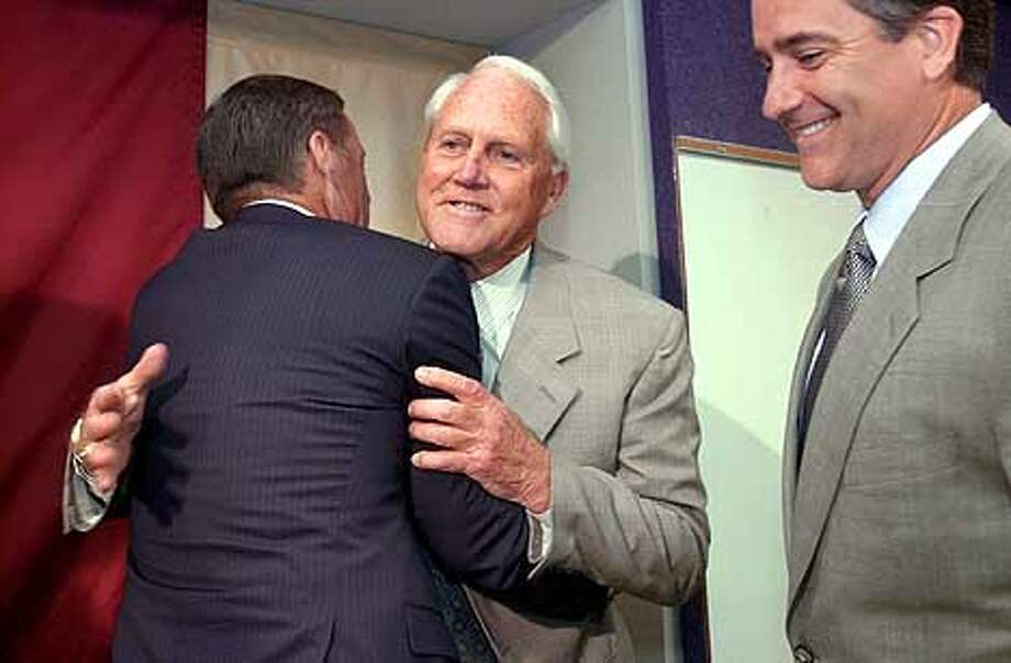 49ers Bill Walsh, center, hugs new 49ers General Manager Terry Donahue, left as 49ers Head Coach Steve Mariucci looks on, at a press conference announcing the move in Santa Clara. Chronicle Photo by Darryl Bush Photo: Darryl Bush