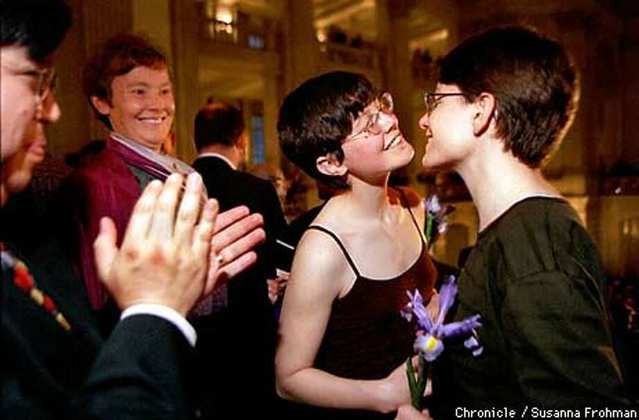 Bethica Quinn and her partner, Caroline Ayres, kissed after their vows as Supervisor Michael Yaki applauded at a city-sponsored mass wedding for lesbians and gay ment at City Hall Friday. Chronicle Photo by Susanna Frohman
