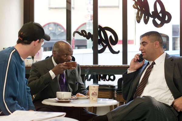 Mayor Willie Brown relaxes and sips on a mocha at Caffe Roma in the North Beach area after casting his vote in Chinatown. He sits with press secretary PJ Johnston (left) and Fred Hamdun (right), Brown's campaign manager.