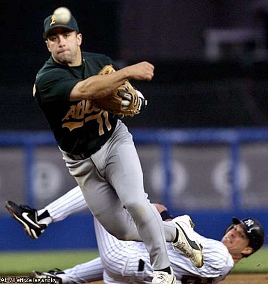 A's second baseman Frank Menechino threw to first to complete a double play on Tino Martinez, bottom, and Jorge Posada in the second inning. Associated Press photo by Jeff Zelevansky