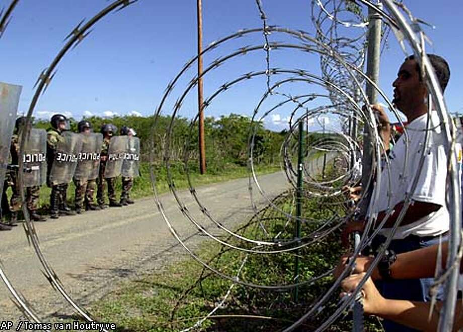 Military police in riot gear watched protesters through the perimeter fence at Camp Garcia on Vieques island, Puerto Rico, where the U.S. Navy has resumed at least four days of bombing exercises. Associated Press photo by  Tomas van Houtryve
