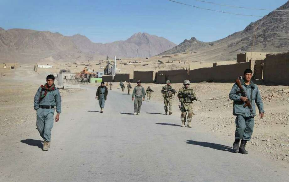 FILE - Afghan policemen walk ahead of the U.S. soldiers with the NATO- led International Security Assistance Force (ISAF) during a foot patrol in Kandahar, south of Kabul, Afghanistan, in this Jan. 7, 2012 file photo. In testimony prepared for delivery Wednesday Feb. 1, 2012 to the House Armed Services Committee, defense officials said that in most cases the Afghans acted out of personal motivation and were not controlled or directed by insurgent groups. The second most common circumstances involved insurgents impersonating or infiltrating Afghan security forces. Photo: AP