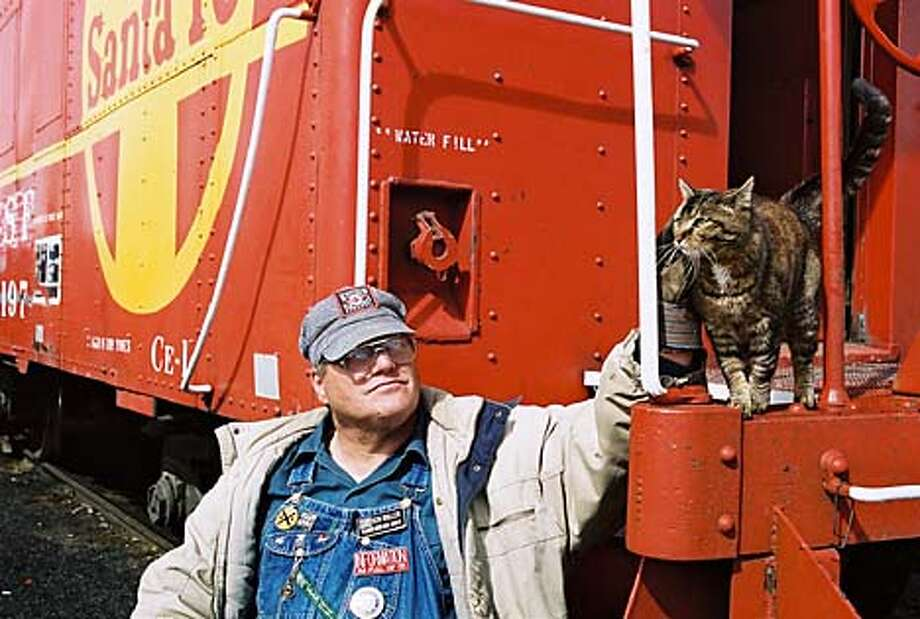Ken Roller, caretaker of the Portola Railroad Museum, strolls the 37-acre grounds - but never without his cat, Hotbox. Chronicle photo by Michael Dougan