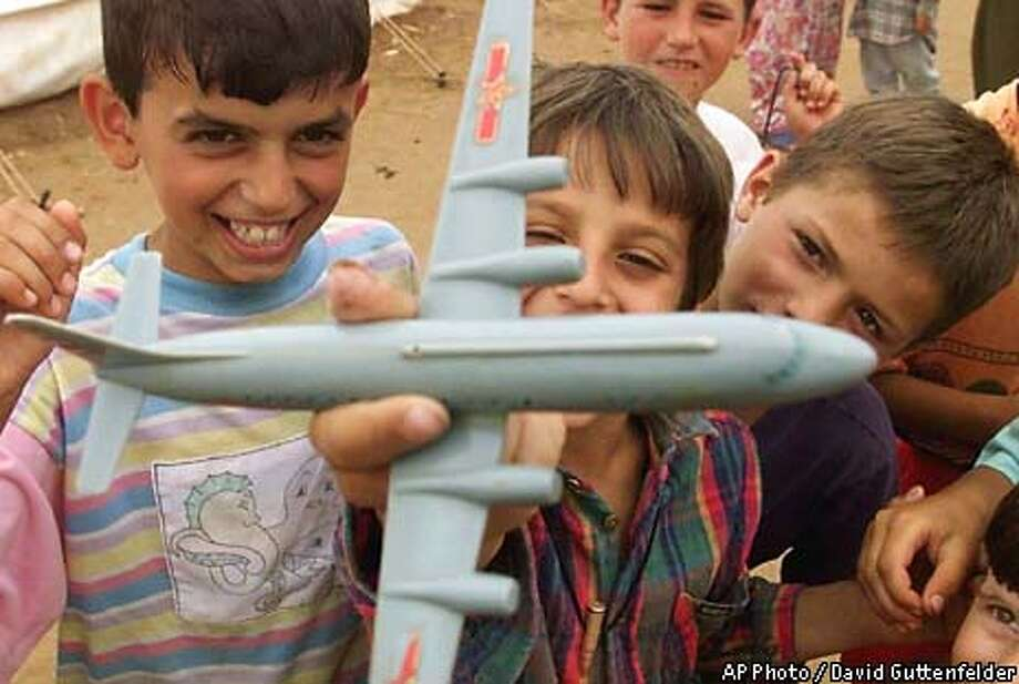 Ethnic Albanian children living in a Kukes, Albania, refugee camp play with a toy bomber airplane Tuesday June 8, 1999. NATO has stepped up its air campaign in the southwestern part of Kosovo along the Albanian border eusing B-52 bombers where Serb forces are battling with the Kosovo Liberation Army. (AP Photo/David Guttenfelder) Photo: DAVID GUTTENFELDER