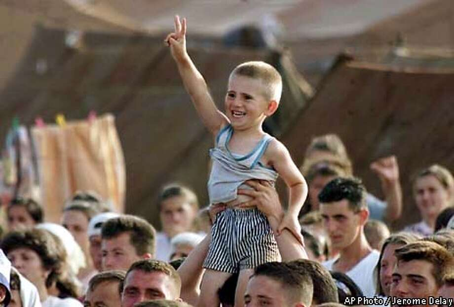 """A young ethnic Albanian refugee smiles as he flashes the """"V"""" sign during a children's patriotic song and poetry show at the United Arab Emirates camp on the ouskirts of Kukes, Albania Friday, June 4, 1999. Even with a peace agreement in place, a shattered Kosovo infrastructure and concerns about security could prevent the early return of more than 855,000 refugees to their Kosovo homeland, U.N. officials said Friday. (AP Photo/Jerome Delay) Photo: JEROME DELAY"""
