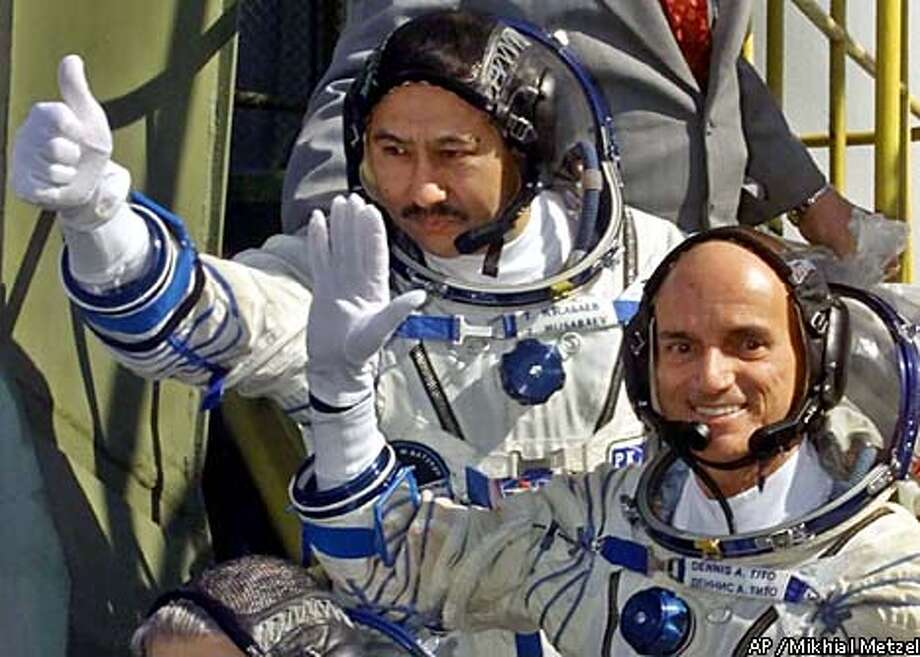 Cosmonaut Talgat Musabaev, top, and American space tourist Dennis Tito waved as they boarded the Soyuz rocket. Associated Press photo by Mikhial Metzel