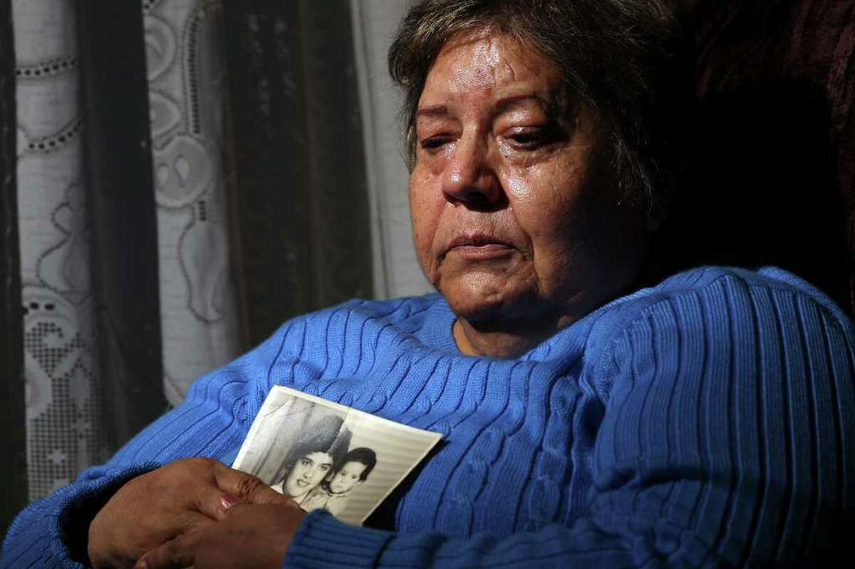 METRO -- Francisca Acosta Mejia, 68, holds an old photograph of her sister, Ana Maria Acosta, 70, in her apartment off Fredericksburg Road, Thursday, Jan. 19, 2012. Her sister died as a a passenger in a car where the driver was distracted by a cell phone. The photograph dates back 50 year and Acosta is with her then one-year-old son Jerry Lara/San Antonio Express-News
