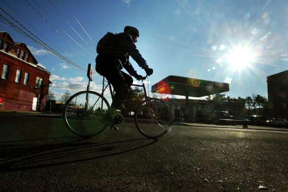 Connecticut Post reporter John Burgeson commutes down East Main St. in Bridgeport from his Stratford home as he commutes by bike to the newspaper office at 8 a.m. on Monday, January 30, 2012. Photo: B.K. Angeletti / Connecticut Post