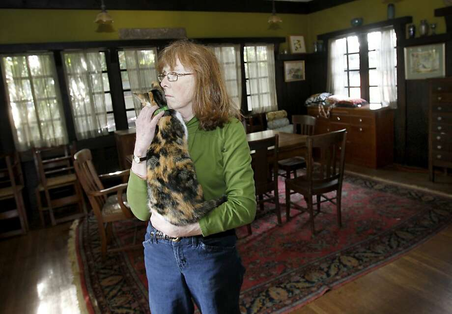 Jane Powell stands in the dining room of her home with one of her beloved cats. Oakland Calif. author and preservation activist Jane Powell has pumped blood, sweat and tears into her 1905 bungalow, but illness and a poor economy may force her to lose this historic home. Photo: Brant Ward, The Chronicle