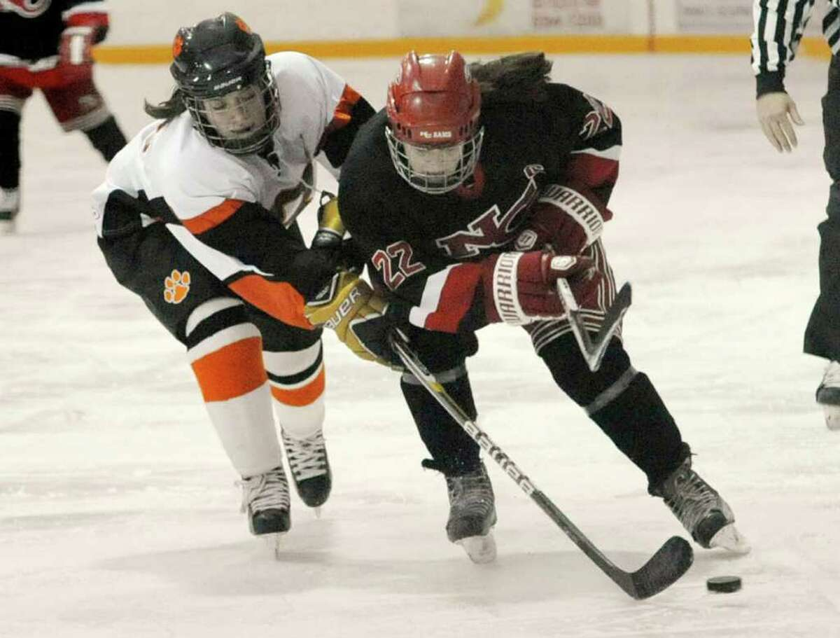Ridgefield's Anna Marcus gets a stick on the puck while guarding New Canaan's Olivia Hompe during their game at the Ridgefield Winter Garden on Wednesday, Feb. 1, 2012. New Canaan won 4-2.