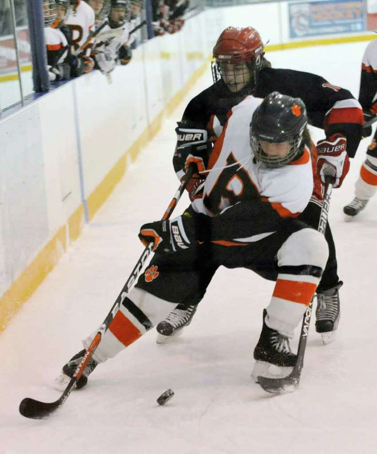 Ridgefield's Meghan Galloway shields the puck from New Canaan's Holly Burwick during their game at the Ridgefield Winter Garden on Wednesday, Feb. 1, 2012. New Canaan won 4-2.