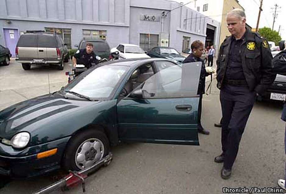 Berkeley police officers collected evidence from a car which was recovered in Emeryville about one hour after it was stolen in Berkeley. A baby still inside the vehicle was found unharmed.  PAUL CHINN/S.F. CHRONICLE Photo: PAUL CHINN